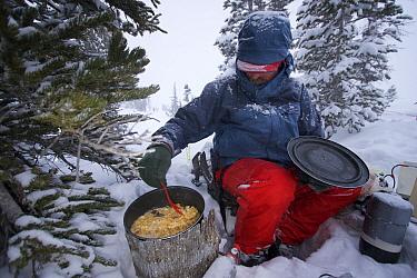 Phil Atkinson preparing dinner during a snow storm at a camp near Denny Lake, Beartooth Mountains, Montana, USA. May 2008