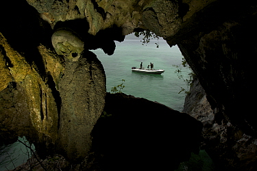 Skull cave with a human skull embedded in the wall, with Triton bay and diving tender visible in background. Raja Ampat, West Papua, Indonesia, May 2007