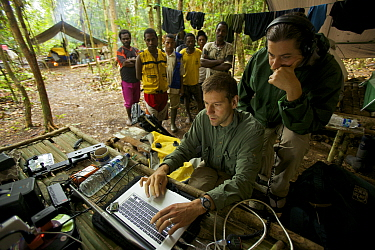 Eric Liner reviews footage on his laptop, while Edwin Scholes and villagers look on. West Papua, New Guinea, August 2009