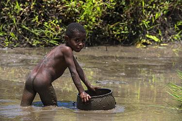 Dani tribe boy in river, Budaya village, Suroba, Trikora Mountains, West Papua, Indonesia. March 2018.