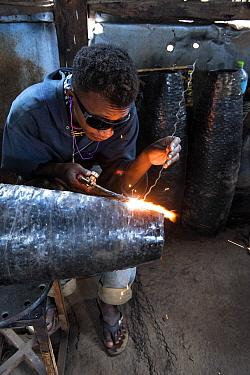 Deaf worker, in metal factory, making metal artefacts for tourist industry, Antananarivo, Madagascar. October 2018.