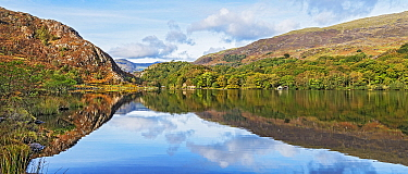 Reflections in Llyn Dinas on a still morning in the Nant Gwynant valley near Beddgelert, Snowdonia, North Wales, UK October 2018