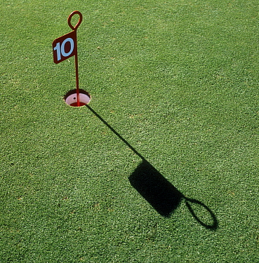 Number 10 marker, hole and long shadow in close mown grass turf of a golf practice putting green, Surrey, October