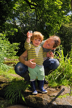 Young boy held by mother as he holds up a collecting pot after a pond-dipping session during Abbots Pool and woodland reserve Bioblitz, Bristol, June, Bristol, UK, June 2012. Model released.