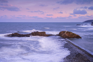 Bude breakwater and Barrel Rock at high tide, sunearise colour, Bude, Cornwall, UK. January 2021.