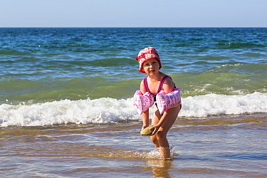 Young girl with armbands playing with stone on the beach. Biarritz, Aquitaine, France, September 2014. Model released.