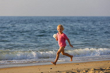 Young girl running along beach with soft toy. Biarritz, Aquitaine, France, September 2014. Model released.