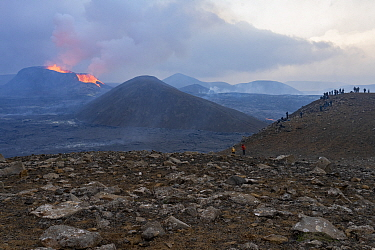 Group of hikers viewing volcanic eruption in distance. Volcano has been dormant for 6000 years, Iceland, Fagradalsfjall Volcano, Europe, 7 June-2021.