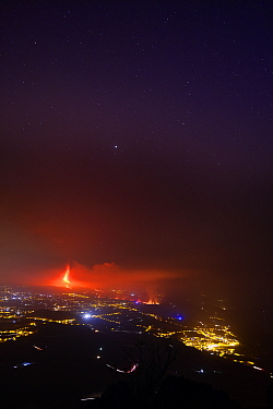 Aerial view of Cumbre Vieja volcano erupting at night, with lava flowing though El Paso village, La Palma Island, Canary Islands, Spain. September 2021.