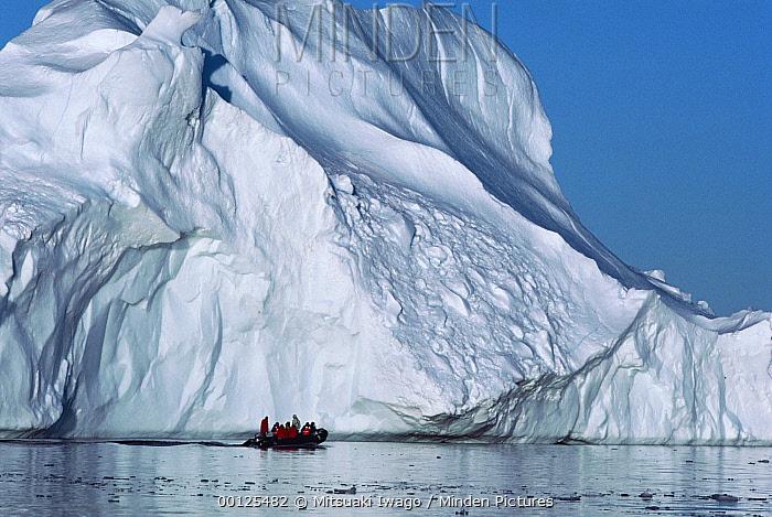 Tourists in an inflatable zodiac boat approaching an iceberg, Antarctica  -  Mitsuaki Iwago
