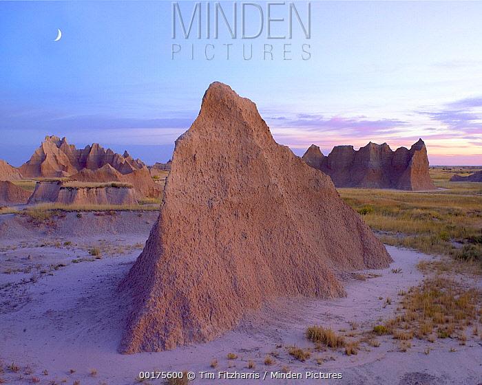 Crescent moon over landscape showing erosional features, Badlands National Park, South Dakota  -  Tim Fitzharris