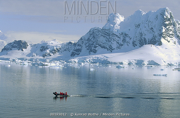 Tourists in zodiac boat with snow covered landscape, Paradise Bay, Antarctica  -  Konrad Wothe