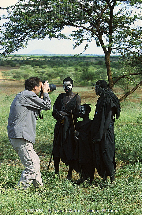 Tourist photographing young Masai tribesmen in typical dress and body paint after circumcision, Tanzania  -  Konrad Wothe