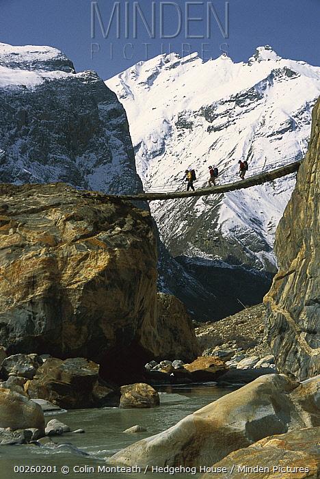 Trekkers cross a swing bridge over the Braldu River en route to Baltoro Glacier, Karakoram Mountains, Pakistan  -  Colin Monteath/ Hedgehog House