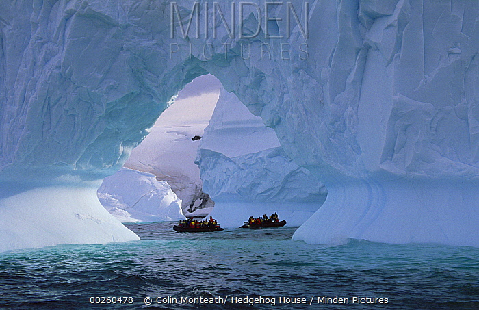 Tourists cruise in inflatable boats, close to large iceberg arch, Enterprise Island, Antarctica Peninsula, Antarctica  -  Colin Monteath/ Hedgehog House