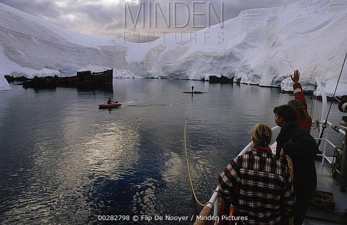 Tourists on cruise ship waving to others in zodiac, Gerlache Strait, Antarctica  -  Flip de Nooyer