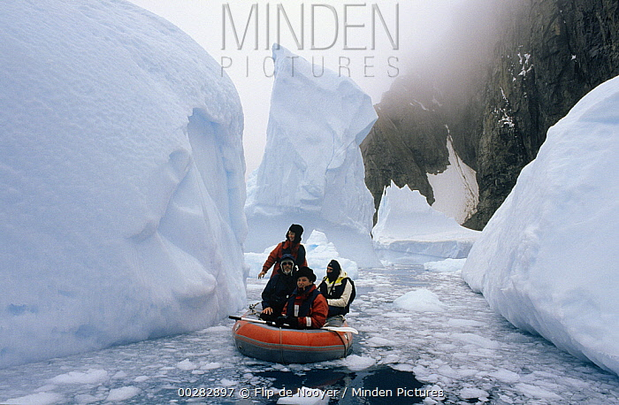 People in inflatable boat in icy seas, Trinity Island, Antarctica  -  Flip de Nooyer