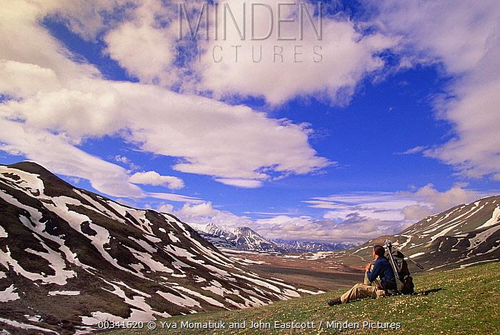 Alaska Range in spring snow, photographer resting in valley below mountains, Denali National Park and Preserve, Alaska  -  Yva Momatiuk & John Eastcott