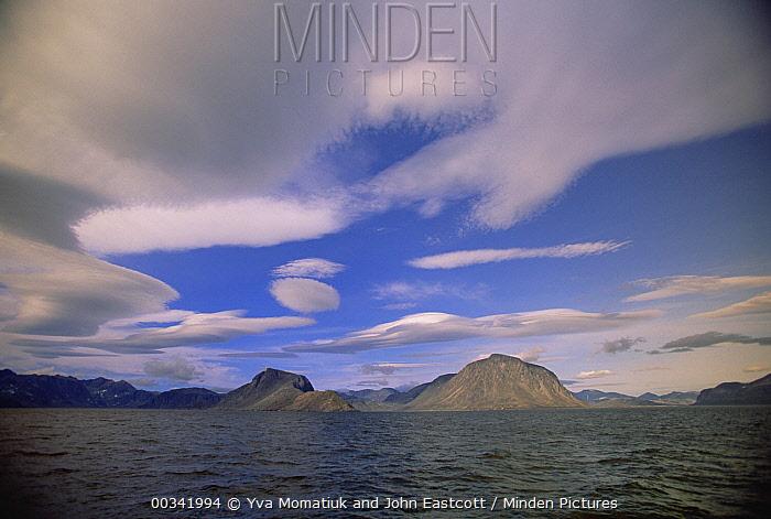 Granite mountain beneath lenticular clouds, surrounding Eclipse Harbor and Torngat Mountain, site of proposed national park, summer, Labrador Sea, Labrador, Newfoundland, Canada  -  Yva Momatiuk & John Eastcott