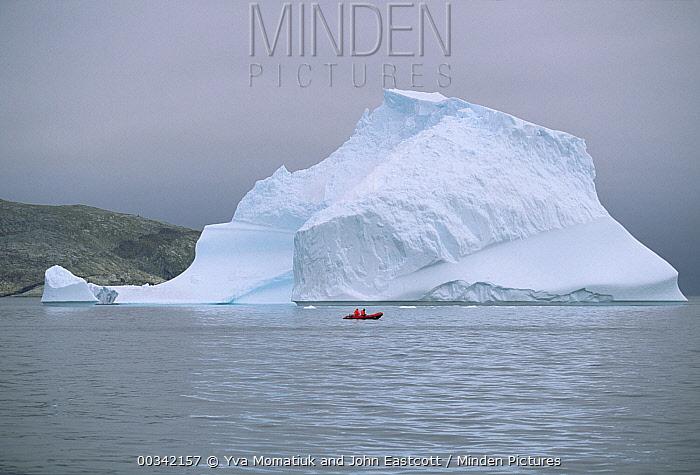 Red rubber boat with two expedition members circle floating iceberg, summer season, Labrador Sea, Labrador, Canada  -  Yva Momatiuk & John Eastcott