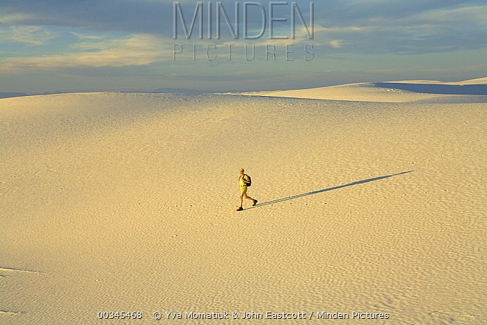 Man hiker wearing shorts, a hat and a backpack, 52, walking alone in a big sprawling landscape of sand and distant mountains, across white sand dunes, evening, autumn, White Sands National Monument, New Mexico  -  Yva Momatiuk & John Eastcott