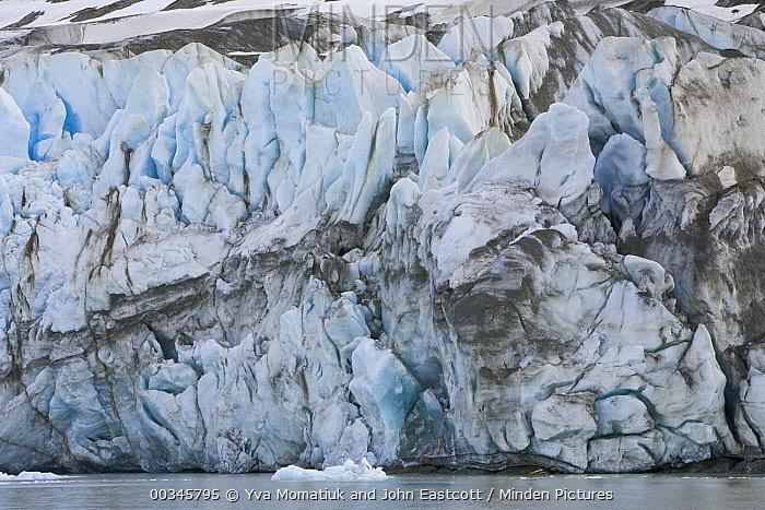 Crumbling blocks and wall of blue glacier marked by morraine debris descending toward sea, Neumayer Glacier, South Georgia Island  -  Yva Momatiuk & John Eastcott