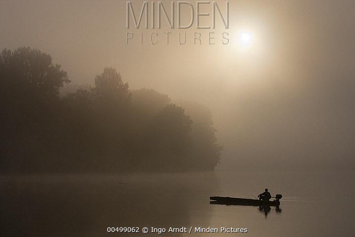 Fisherman on Tisza River on foggy morning, Hungary  -  Ingo Arndt
