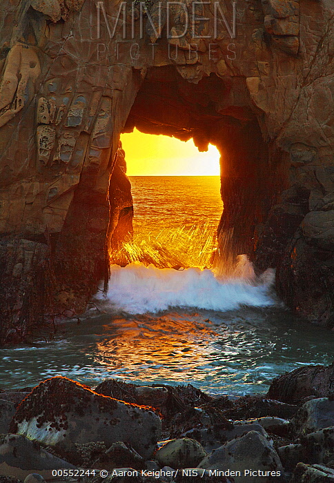 Wave crashing through Keystone Arch at sunset, Pfeiffer Beach, Big Sur, California