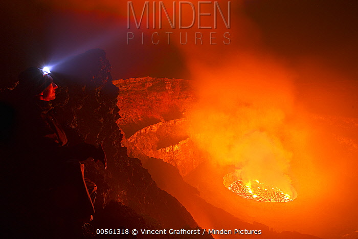 Man looking into crater at night, Mount Nyiragongo, Virunga National Park, Democratic Republic of the Congo