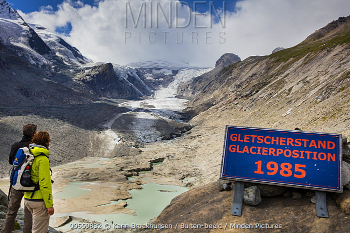 Tourists with sign indicating the extent of glacier in 1985, Winkl, Austria