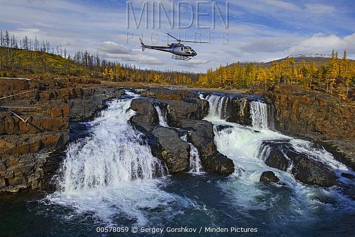 Helicopter flying over waterfall in taiga, Putoransky State Nature Reserve, Putorana Plateau, Siberia, Russia