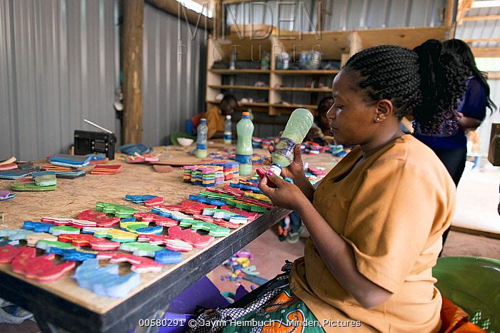 Artist working on sculptures made from reclaimed flip-flops, Ocean Sole, Nairobi, Kenya