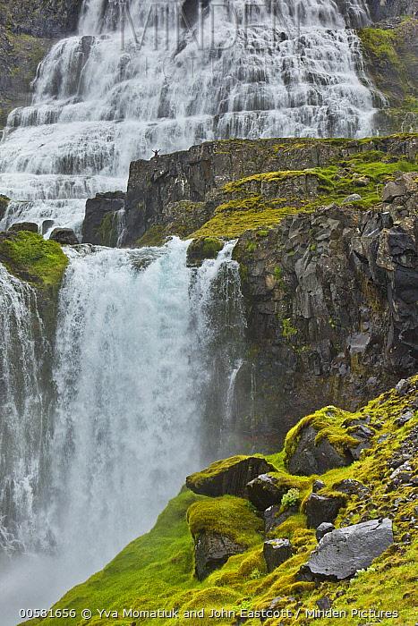 Tourist next to cascades, Dynjandi Waterfall, Westfjords, Iceland