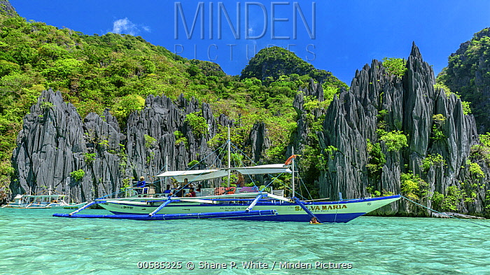 Tourists on boat in tropics, Cadlao Island, Philippines