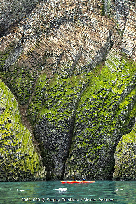 Kayakers looking at moss-covered basalt cliffs, Franz Josef Land, Russia