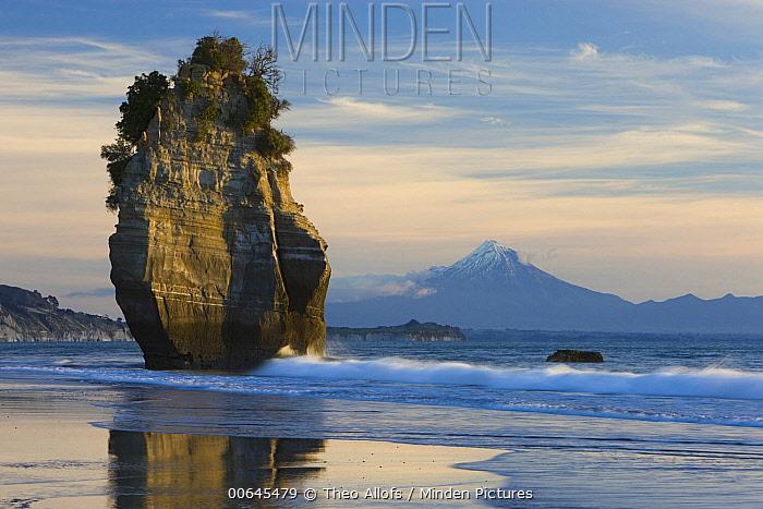 Sea stack on beach with Mount Taranaki, New Zealand