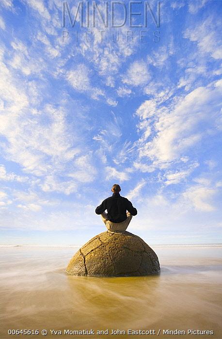 Man meditating on boulder under cumulus clouds, Koekohe Beach, Otago, South Island, New Zealand, digital composite