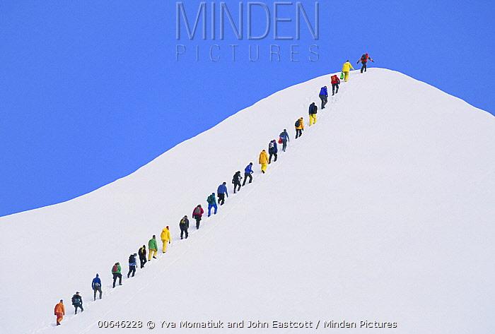 Hikers ascend snowy peak, North America, digitally manipulated