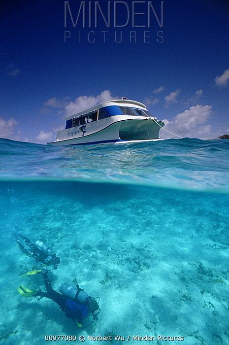 Scuba divers Leslie Davies and Alison Jenkin swim beneath new catamaran speedboat, British Virgin Islands  -  Norbert Wu