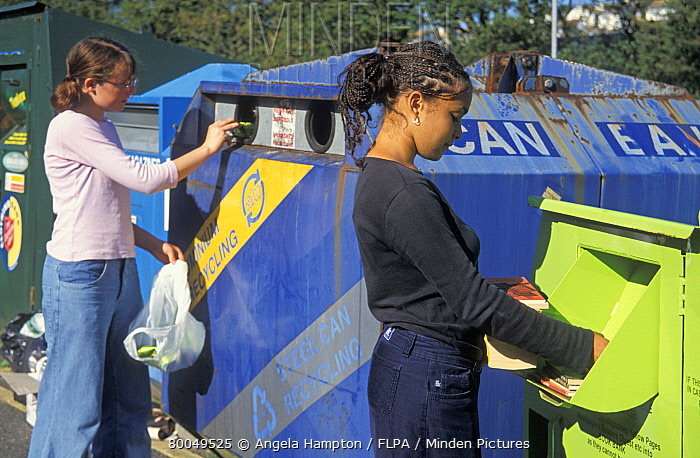 Recycling, teenage girls, putting unwanted books and bottles into recycling bins, England  -  Angela Hampton/ FLPA