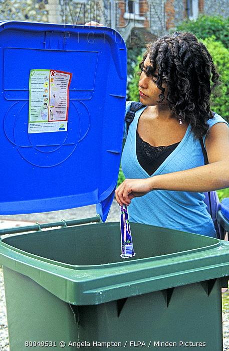Recycling, young woman putting waste paper into recyle bin, England  -  Angela Hampton/ FLPA