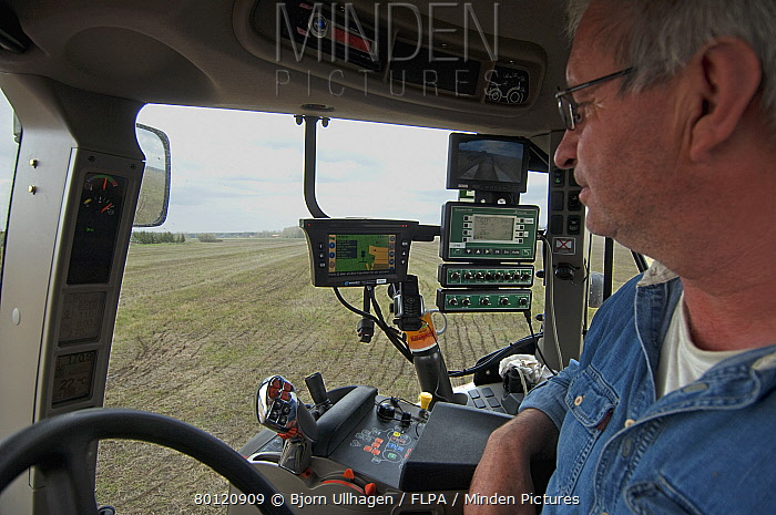 Case tractor interior and farmer, with GPS and Samson vacuum slurry tanker control panel, injecting slurry into stubble field, Sweden, may  -  Bjorn Ullhagen/ FLPA