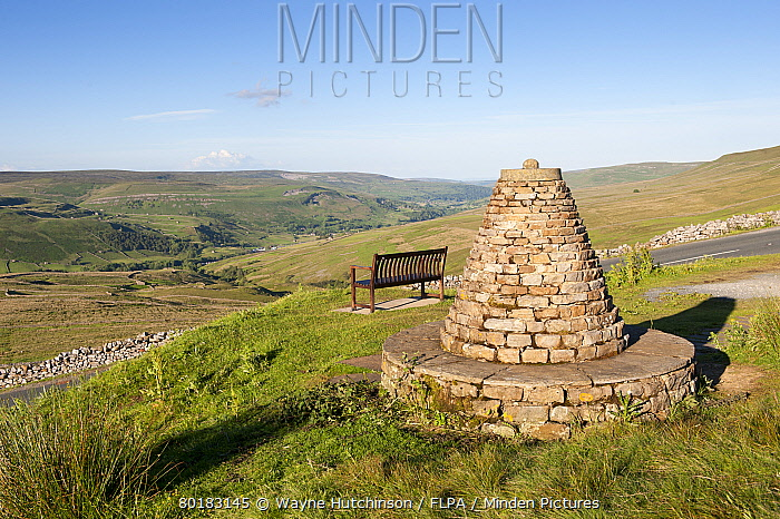 Cairn and bench on upland viewpoint overlooking valley, marking boundry of Muker Parish, Millennium Cairn, Buttertubs Pass, Swaledale, Yorkshire Dales National Park, North Yorkshire, England, July  -  Wayne Hutchinson/ FLPA