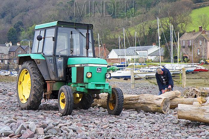 John Deere 1640 tractor and man chopping up driftwood deposited on beach, Porlock, Bristol Channel, Somerset, England, March
