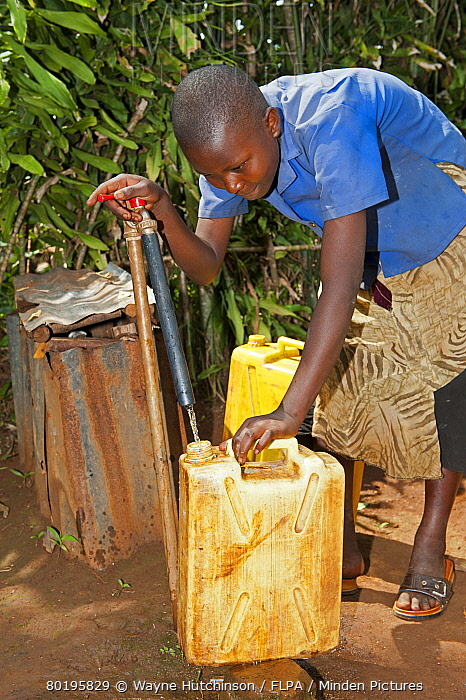 Rwandan girl filling container with fresh water from a tap.