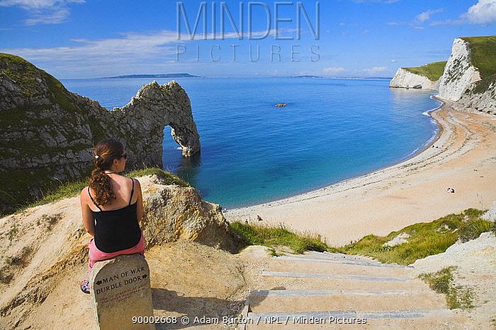 Woman resting on clifftop sign, looking towards Durdle Door beach, Dorset, England Jurassic Coast World Heritage Site Model released  -  Adam Burton/ npl