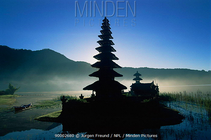 Ulu Danau temple on shore of Lake Bratan, Bali, Indonesia at sunrise with mist over lake  -  Jurgen Freund/ npl