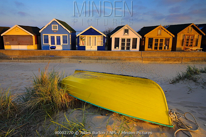 Beach huts and upturned boat on Mudeford Spit, Dorset, England  -  Adam Burton/ npl