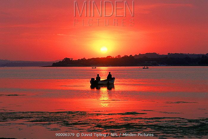 Fishing boats, silhouette on Rutland Water at sunset England  -  David Tipling/ npl