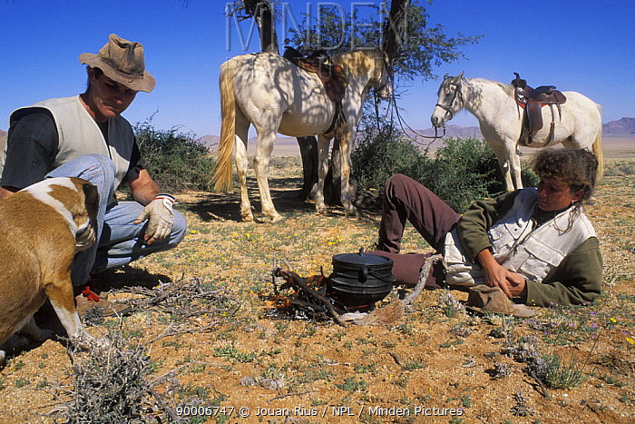 Two people with horses (Equus caballus) and a dog, cooking and taking a rest stop from riding, Namib desert, Namibia  -  Jouan & Rius/ npl